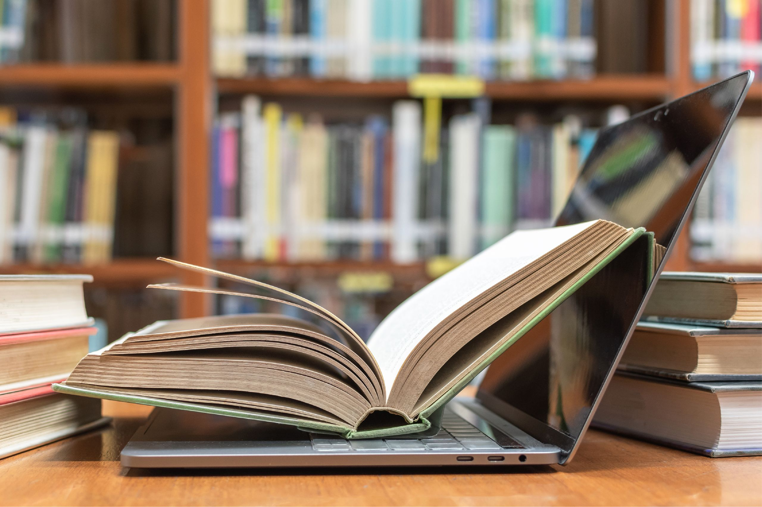 book resting on laptop in library